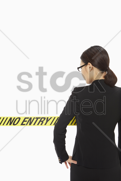 businesswoman standing behind a no entry sign stock photo
