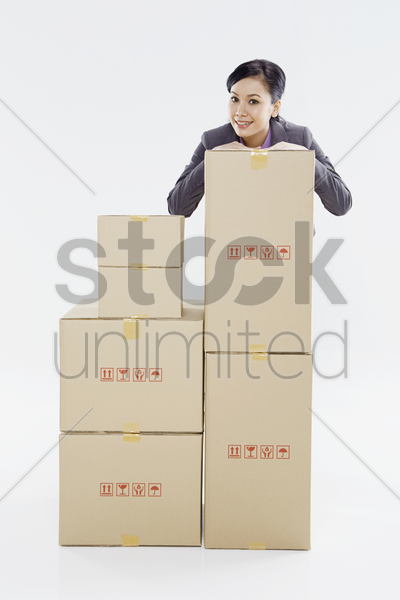 businesswoman standing behind a stack of boxes stock photo