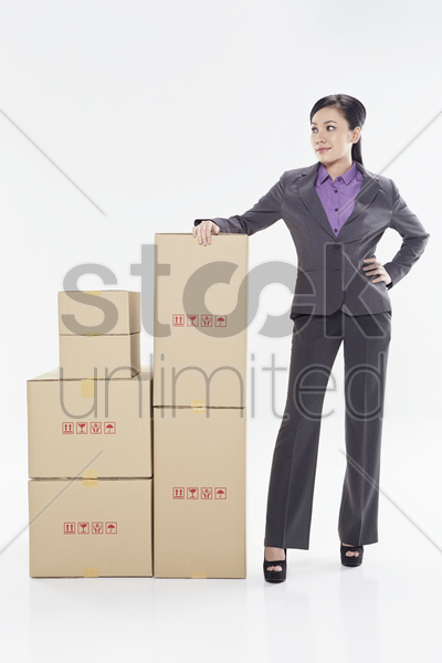 businesswoman standing beside a stack of boxes stock photo
