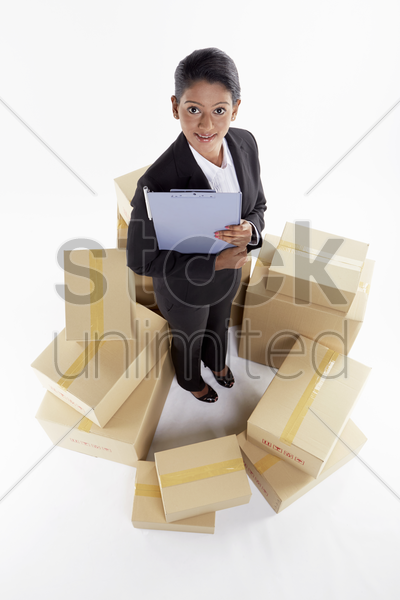 businesswoman standing in the middle of cardboard boxes stock photo