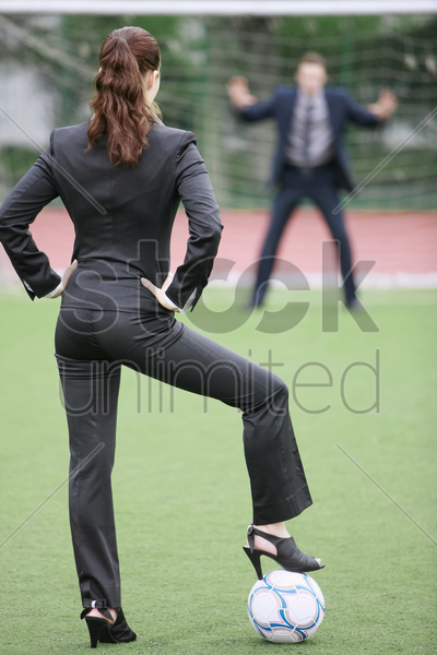 businesswoman standing on football with businessman as the goal keeper stock photo