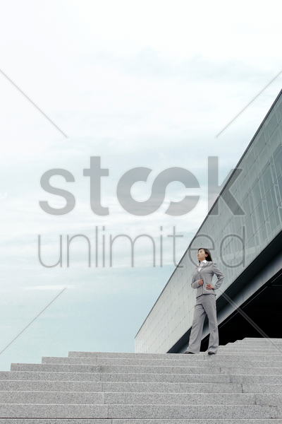 businesswoman standing on the stairs stock photo