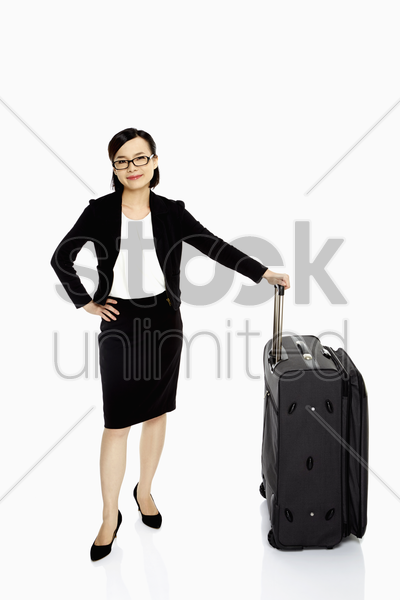 businesswoman standing with a luggage bag, smiling stock photo
