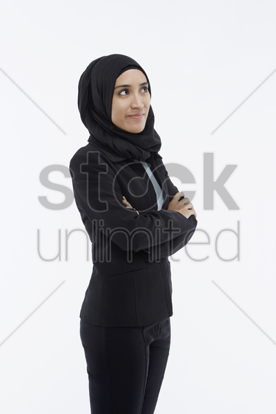 businesswoman standing with arms crossed, contemplating stock photo
