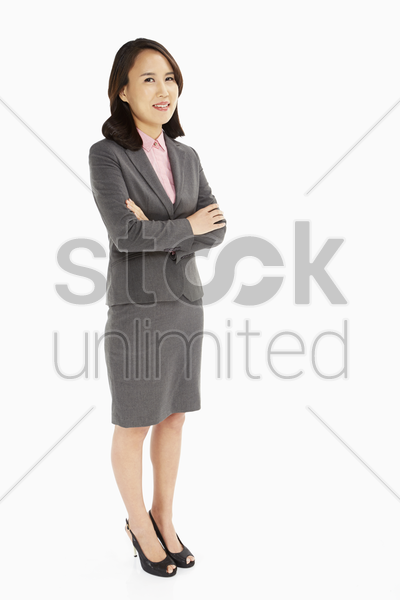 businesswoman standing with arms crossed, smiling stock photo