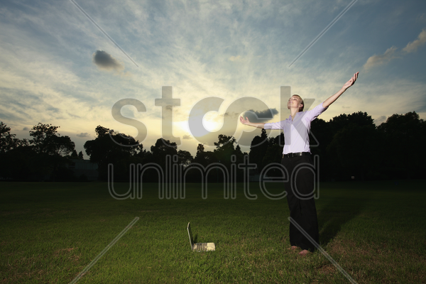 businesswoman standing with her arms outstretched stock photo