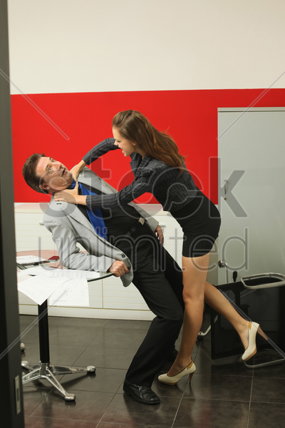 businesswoman strangling businessman at a table stock photo