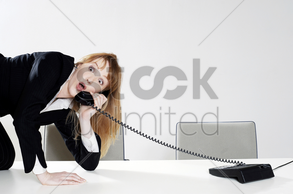 businesswoman struggling to answer a phone call stock photo