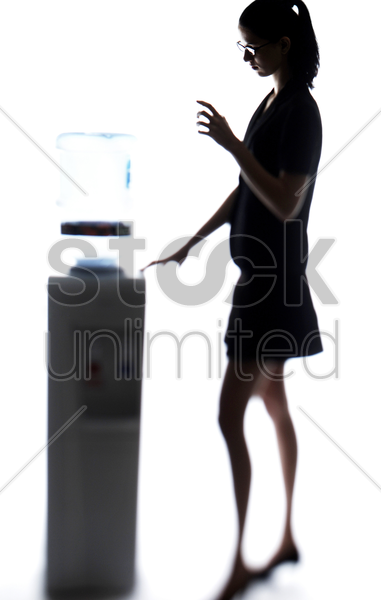 businesswoman taking water from the water dispenser stock photo