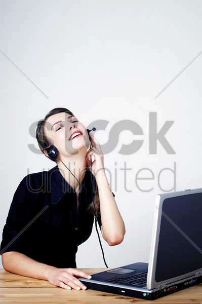 businesswoman talking on telephone headset and using a laptop stock photo