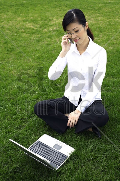 businesswoman talking on the mobile phone while using laptop stock photo