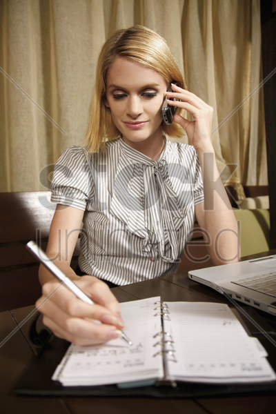 businesswoman talking on the phone while writing in organizer stock photo