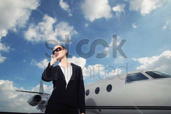 businesswoman talking on the phone with private jet in the background stock photo