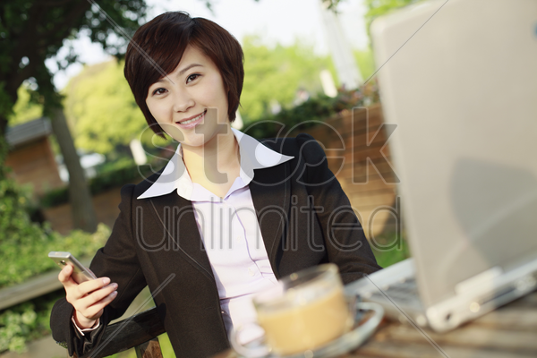 businesswoman text messaging and smiling stock photo