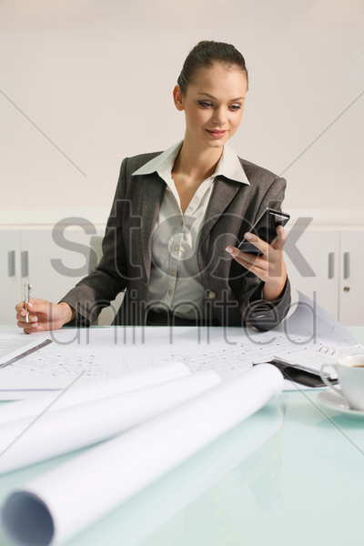businesswoman text messaging on the mobile phone stock photo