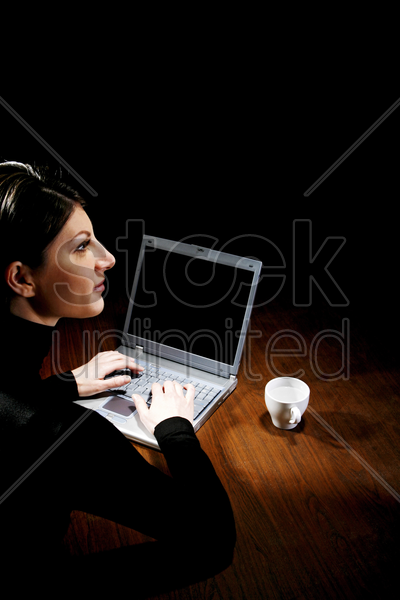 businesswoman thinking while using laptop stock photo