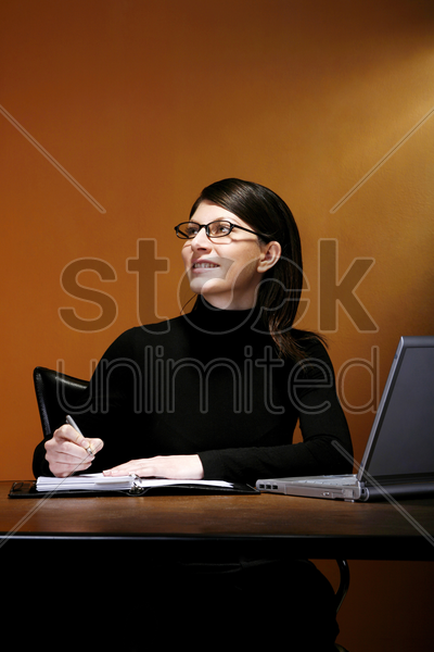 businesswoman thinking while writing stock photo