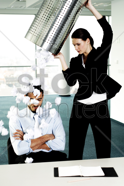 businesswoman throwing a dustbin of crumpled papers on her colleague stock photo