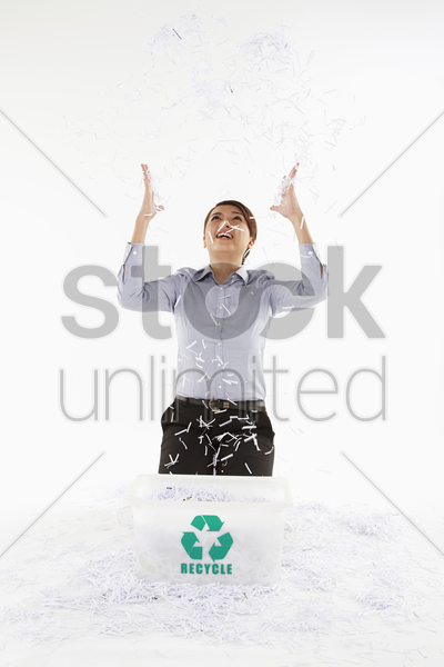 businesswoman throwing shredded paper in the air stock photo