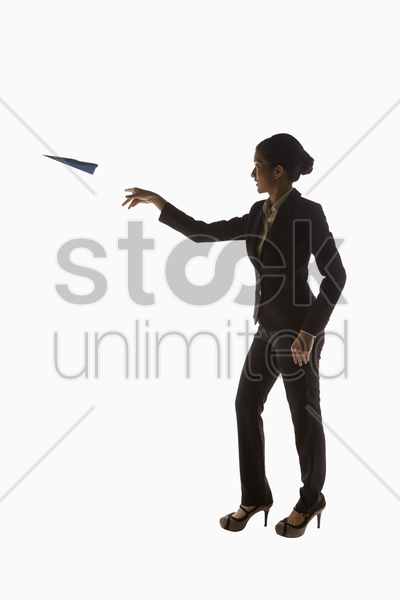businesswoman tossing a paper airplane stock photo
