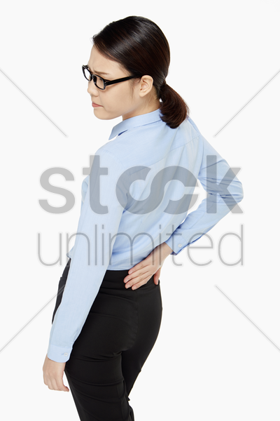 businesswoman touching her lower back stock photo