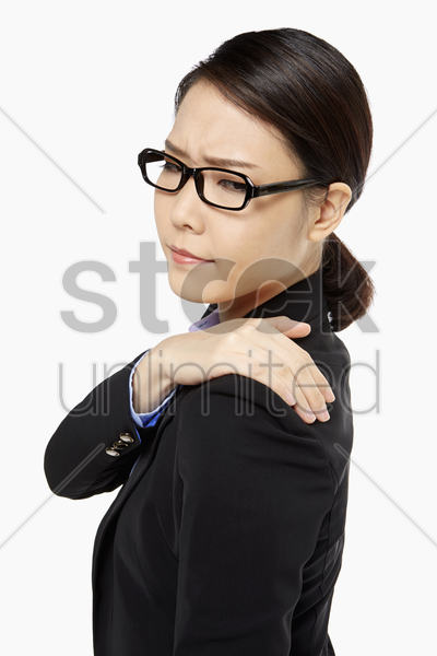 businesswoman touching her painful shoulder stock photo