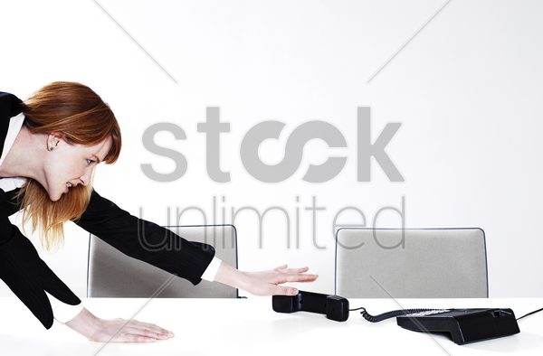 businesswoman trying to reach out for the phone stock photo