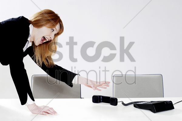 businesswoman trying to reach the phone receiver stock photo