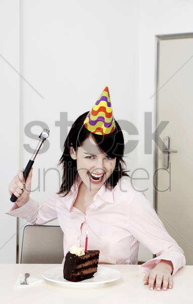 businesswoman trying to smash her cake with a hammer stock photo