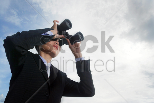 businesswoman using binoculars stock photo
