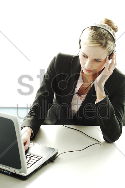 businesswoman using headset and laptop stock photo