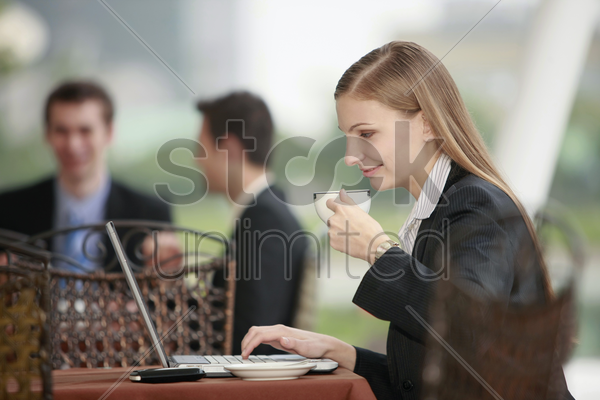businesswoman using laptop and enjoying coffee at outdoor cafe stock photo