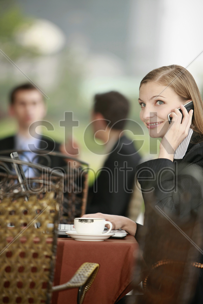 businesswoman using laptop and talking on the phone at outdoor cafe stock photo