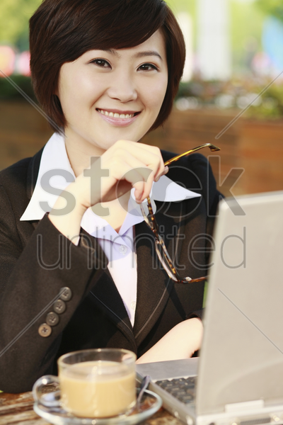 businesswoman using laptop at an outdoor cafe stock photo