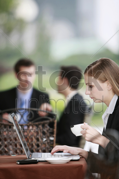 businesswoman using laptop at outdoor cafe stock photo