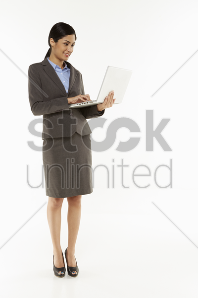 businesswoman using laptop, smiling stock photo