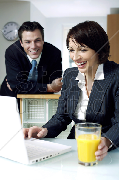 businesswoman using laptop with her husband in the background stock photo