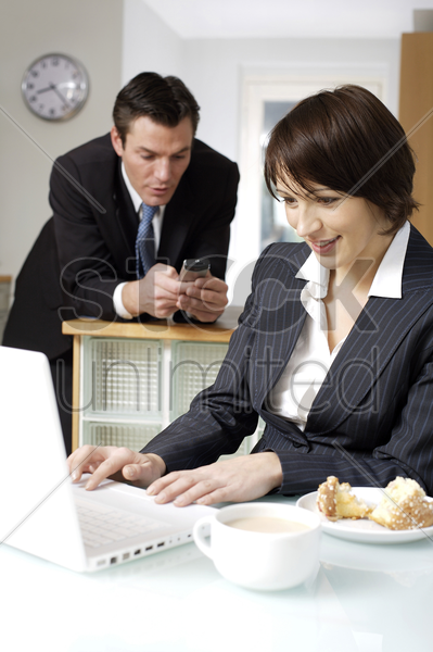 businesswoman using laptop with her husband text messaging in the background stock photo