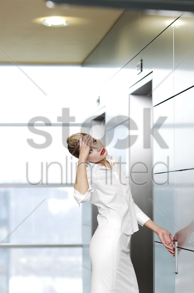 businesswoman waiting for elevator stock photo