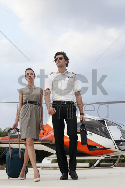 businesswoman walking away from helicopter with pilot stock photo