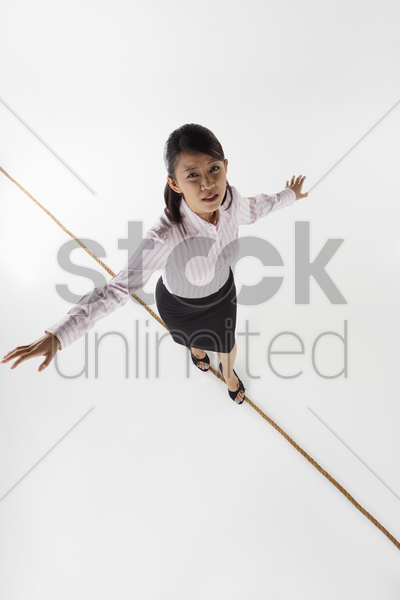businesswoman walking on a tightrope, worried stock photo