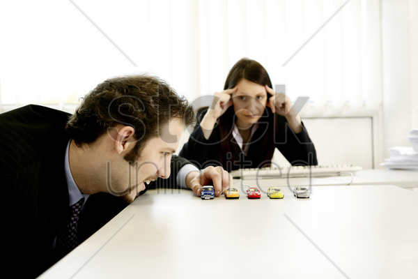 businesswoman watching her male colleague playing with his toy cars stock photo