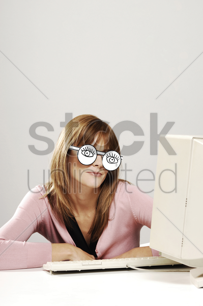 businesswoman wearing a cardboard cut-out spectacles while using computer desktop stock photo