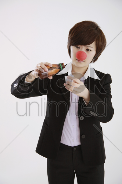 businesswoman wearing a clown's nose taking cough syrup stock photo