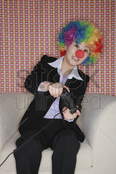 businesswoman wearing a clown's wig and nose playing video game stock photo