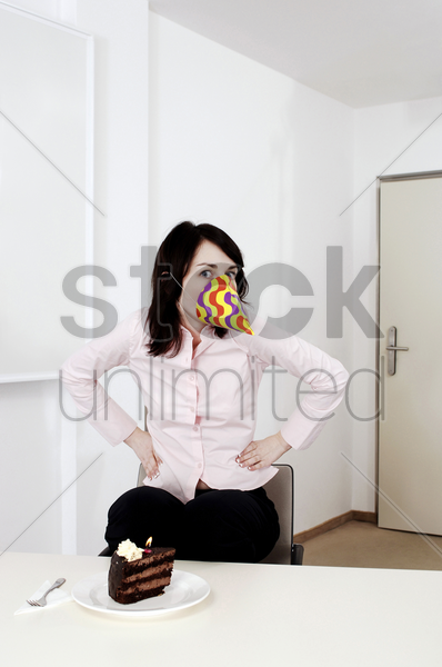 businesswoman wearing a party hat on her face stock photo