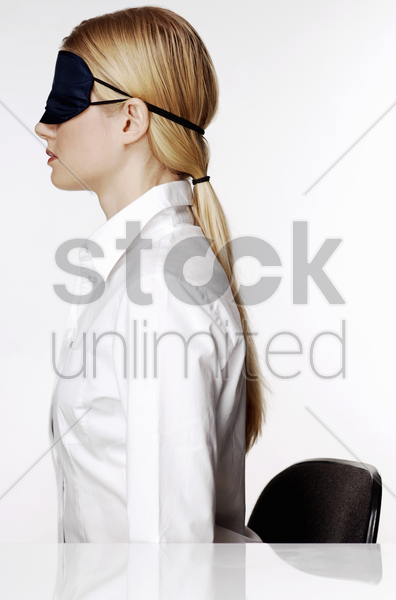businesswoman wearing eye mask stock photo