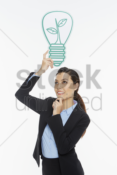 businesswoman with a cut out light bulb, contemplating stock photo