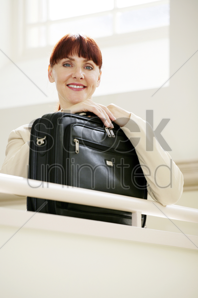businesswoman with a laptop bag looking at the camera stock photo