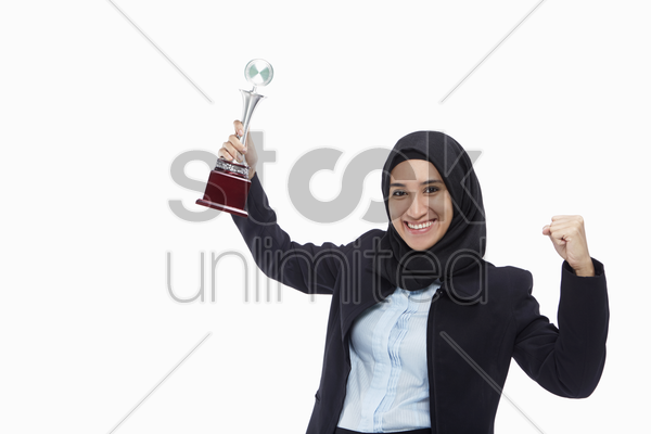 businesswoman with a winning trophy, smiling and cheering stock photo